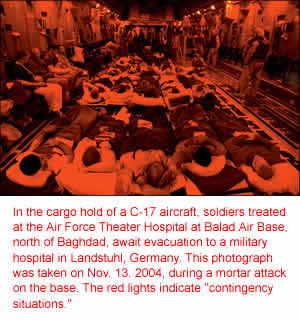 In the cargo hold of a C-17 aircraft, soldiers treated at the Air Force Theater Hospital at Balad Air Base, north of Baghdad, await evacuation to a military hospital in Landstuhl, Germany. This photograph was taken on Nov. 13, 2004, during a mortar attack on the base. The red lights indicate ''contingency situations.''